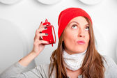 Beautiful brunette in a red hat listening alarm clock — Stock Photo