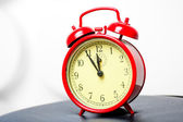 Red alarm clock in a retro style shot in a studio — Stok fotoğraf
