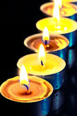 Number of hot yellow candles in the dark — 图库照片