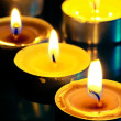 Small yellow burning candle in the dark — Stock Photo