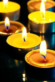 Small yellow burning candle in the dark — Stock fotografie