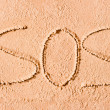 SOS written in the sand on the beach in large letters — Stock Photo