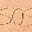 SOS written in the sand on the beach in large letters — Stock Photo #40026247