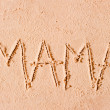 Child wrote the word mom in the sand on the beach — Stock Photo #40026405