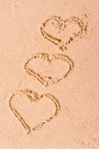 Three hearts drawn on wet sand — Stock Photo