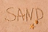 ビーチの砂とヒトデに書かれた単語 — ストック写真