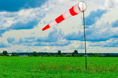 Striped windsock in a green field — Stock Photo