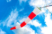 Blue sky and striped windsock — Stock Photo