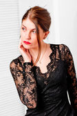 Woman in lace black dress looking to the side — 图库照片