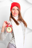 Girl in scarf and hat shows the time on the alarm clock — Stock Photo