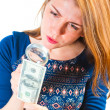 Girl carefully considering the money through a magnifier — Stock Photo