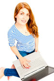 Charming girl with a computer on white background — Stock Photo