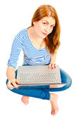 A charming young girl on a white background with a laptop — Stock Photo