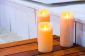 Three burning candles on a wooden table — Foto de Stock