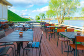 Urban riverfront cafes and green trees — Stock Photo