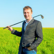 Happy businessman with a golf club in the field — Stock Photo #48197759