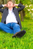 Businessman relaxes on a green lawn — Stock Photo