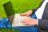 Hands on the laptop in a park close-up — Stock Photo