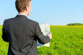 Strayed man seeking to map the way in the field — Stock Photo