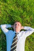 Man i en slips som sover på gräsmattan — Stockfoto