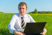 Manager works on nature with laptop — Stock Photo