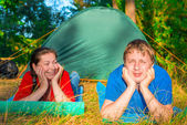 Young people resting on the grass near tent — Stockfoto
