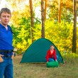 Man and woman among the pines in the campground — Stock Photo #50472765