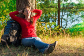 Strongly weary backpacker resting against a tree — Stock Photo