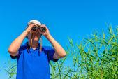 Young hunter looking through binoculars — Stock Photo