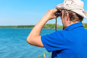 Man with binoculars looks for something on the lake — Stock Photo