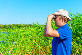 Hunter with binoculars in the reeds — Stock Photo
