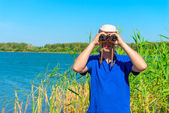 Man in blue shirt is looking out for prey with binoculars — Stock Photo