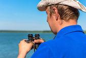 Mladý muž s dalekohledem na povaze — Stock fotografie