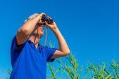 Man with binoculars examines bird in the sky — Stock Photo