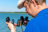 Traveler with a compass and binoculars — Stock Photo