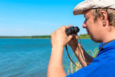 Handsome young man with binoculars at lake — Stock Photo