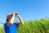 Man looks for through the reeds with binoculars — Stock Photo