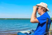 Young man near the lake looking through binoculars — Stock Photo