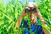Man in an ambush the reeds with binoculars — Stock Photo