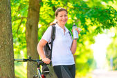 Happy sportswoman with a bottle of water and a bicycle — Stock Photo
