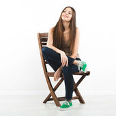 Beautiful young woman sitting on a chair — Stock Photo