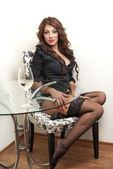 Sexy young brunette woman in black lingerie sitting on stool — Stock Photo