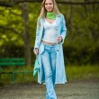 Very attractive young girl posing in jeans and blue coat outdoor in summer.Park outdoor shooting — Stock Photo