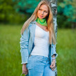 Very attractive young girl posing in jeans and blue coat outdoor in summer.Park outdoor shooting — Stock Photo #12454600