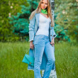 Very attractive young girl posing in jeans and blue coat outdoor in summer.Park outdoor shooting — Stock Photo #12454602
