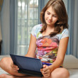 Stock Photo: Young teen girl laying on her bed surfing the internet