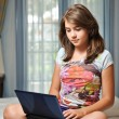 Young teen girl laying on her bed surfing the internet — Stock Photo