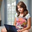 Young teen girl laying on her bed surfing the internet - Stock Photo