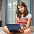 Young teen girl laying on her bed surfing the internet — Stock Photo #13343404