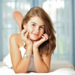 Portrait of smiling beautiful teen girl at home in white dress and relaxing on comfortable bed. Luxury interior. — Stock Photo